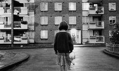 A  girl standing in the middle of a London council estate in the mid-1980s.