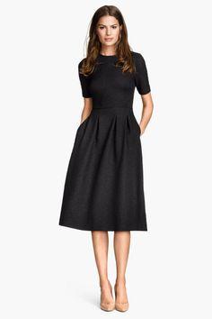 Vestido con textura: Vetsido en punto con textura, mangas cortas, cintura entallada, falda amplia con pliegues en la parte superior y cremallera oculta detrás. Sin forrar. Largo hasta las rodillas.