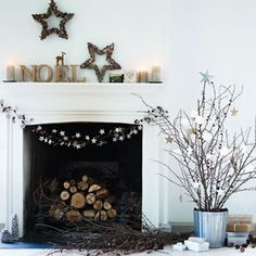 Stars are a classic Christmas decoration. These simple stars at a special touch to this fireplace alongside the festive twig tree. Visit www.redonline.co.uk for more ideas.
