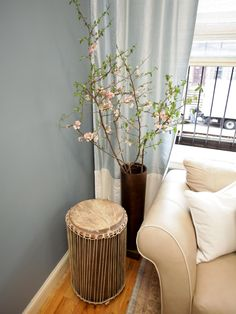 A tribal drum functions as a side table in this soft blue-gray living room. Next to the drum table, a collection of cherry blossom branches adds a touch of femininity to the space.