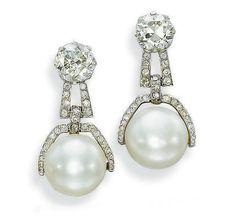 A PAIR OF ELEGANT ART DECO PEARL AND DIAMOND EARRINGS   The two button-shaped pearls measuring 13.45-13.50 x 11.50 and 13.25-13.30 x 10.90 to the pavé-diamond half surround and surmount, with circular-cut diamond tops, mounted in platinum and gold, circa 1925, 3.4 cm high