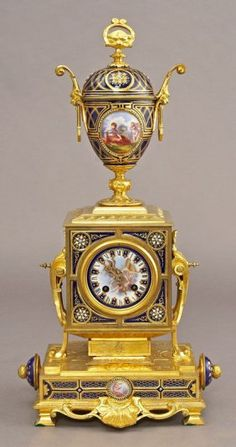 "French jeweled Sevres style mantle clock, the gilt bronze case having figural reserves on cobalt ground porcelain plaques, enameled jewels and ormolu mounts, surmounted by a porcelain urn having a gilt bronze lion's head finial and gargoyle handle mounts; the clock having a porcelain dial with Roman numerals, eight day French movement, stamped, ""GV, 8173"". 24""H, Circa - Late 19th C."