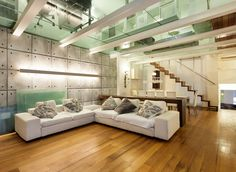Modern living room with wood floors and glass ceiling.