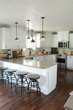 A stunning white kitchen complete with updated pendant lights and smudge-proof Frigidaire appliances. More via http://forcreativejuice.com/elegant-white-kitchen-interior-designs/