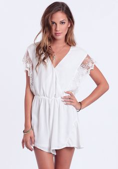 Ethereal white romper featuring floral lace detailing at the sleeves and a subtle ruffled hem. Finished with a V-cut neckline with snap-button closures and an elastic waistband. This AH-mazing ro...