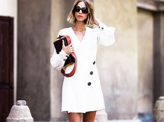 Candela Novembre wears a white kimono wrap dress with a rectangular bag and black sunglasses