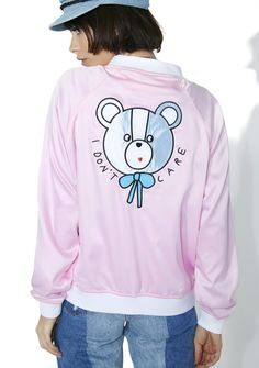 """Lazy Oaf I Don't Care Bear Bomber yew got more important stuff to deal with, bb. Tell 'em how yew feel with this bomber jacket that features a satiny pink construction, banded hem and sleeves, zipper front closure, a lil blue bow on the chest, and """"I Don't Care"""" text on the back underneath a cute bear face."""