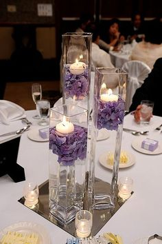 Submerged arrangements like this can be stunning and cost effective. We could do a mixture of something like this, only as you suggested, with more vases (I think 5) on each table, for half of the tables, then fuller low centerpieces for the other half. And candlelight all around! Also, these could be repurposed to line the aisle during the ceremony.