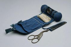 """American glazed leather sewing roll.  Attached scissors holder.  Contains, thimble, scissors and needles.  Probably c. 1860s.  Maximum length: 4-1/2"""""""