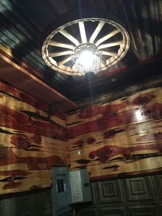 Cedar and tin bathroom, with a light fixture made from an antique wheel.