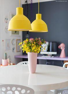 Sala de jantar tem mesa branca com cadeiras descombinadas, parede pintada de cinza e pendentes amarelos da marca Muuto.