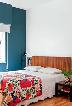 O látex na cor Azul Diesel (ref. P336*), da Suvinil, cobre a mesma parede lateral neste e nos outros dois quartos. Sobre a cama, tecido floral de Ana Morelli.