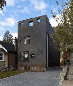 """Surprise entry tucked into an exterior """"corridor."""" Charcoal House, Toronto, ON, by Atelier RZLBD"""