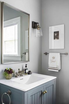 Beautiful gray bathroom features a gray washstand accented with Anthropologie Faceted Ory Knobs and a white quartz countertop fitted with a large sink and a dark nickel faucet.