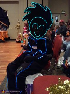 Stacy: This was a cute idea and amazed every one. The face was a mask cut from cardboard and lined with el wire. The suit was a black sweat suit that...