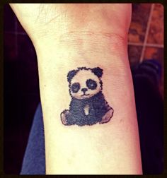 Small panda tattoo on wrist