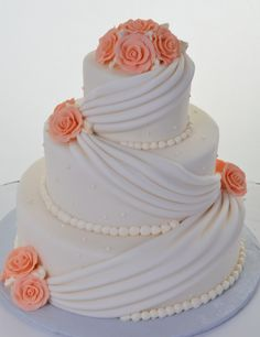 Pastry Palace Las Vegas - Wedding Cake #570 – Drapes & Roses. Three round, white fondant-covered tiers - swagged with matching drapes, icing pearls, and bright peach colored icing roses.