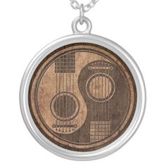 This unique yin yang design features the bodies of two acoustic guitars. The strings of the guitars run up both sides of the pattern with the circular holes visible underneath. The bodies of the guitars take the shape of the yin yang tear drop. Rough textures and natural colors gives the pattern the look of being carved out of aged wood.