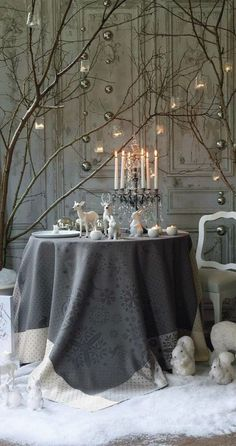 Subtle & sophisticated color scheme-grey, silver, white & clear crystal; charming & whimsical vignette; lovely textural combo with distressed paint backdrop, fabric, tree branches, crystal candelabra & statuary. LOVE this!