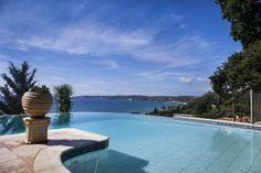 """A paved walk-way around the sunbathing terrace and raised, shaded """"wrap around"""" veranda, overlooking a marvellous free-form, infinity-edged swimming pool that appears to flow off through the pine trees to the Ionian sea below Beach Villa, Beautiful Villas, Terrace, Pine, Flow, Swimming Pools, Infinity, Trees, Shades"""