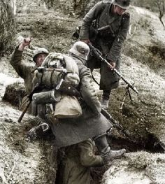 Two Wehrmacht soldiers examining a Soviet trench line during the advance towards Moscow. Note there is also a Soviet soldier still in the trench, who will now become a P.O.W.