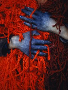 A teenage worker uses dye-stained hands to hold a tangled nest of red yarn. The boy lives in Khulm (formerly Tashkurgan), Afghanistan, a town noted for trade in sheep and wool.