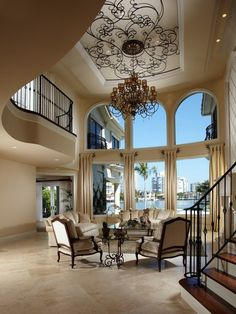 Living room in Mediterranean home with travertine floor and interesting wrought iron scrollwork ceiling detail...