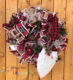 """This cute buffalo plaid Christmas gnome wreath is perfect for all you gnome lovers out there, even better if you're a lover of buffalo plaid and the farmhouse theme. This Christmas gnome wreath is covered in a snowy burlap with beautiful ribbons including a of course the red buffalo plaid, a brown and red snowy covered one, a red and black with the words """"Merry Christmas"""" is also found on the wreath! An Adorable gnome face wearing a buffalo plaid hat sits in the corner of the wreath."""