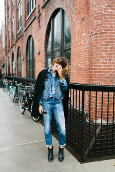 noticed: layering coats and jackets. trace barnhill is wearing a madewell leather-sleeve varsity coat, the classic denim jean jacket, a cozy button-down shirt in blue plaid, and the slim boyjean: rip and repair edition. #denimmadewell