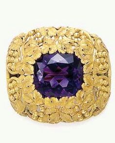 AN AMETHYST AND GOLD BROOCH, BY LOUIS COMFORT TIFFANY, TIFFANY & CO.  Centering upon a cushion-cut amethyst within a textured gold leaf and berry frame, mounted in gold, circa 1910 By Louis Comfort Tiffany; signed Tiffany & Co.