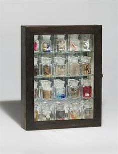 Joseph Cornell (1903-1972)  Pharmacy  typed and dated 'Joseph Cornell 1943' (on a paper label affixed to the inside)  wood box construction -- printed paper, colored sand, colored foil, sulfur, feathers, seashells, butterfly, aluminum foil, fiber, wood shavings, copper wire, fruit pits, water, gold paint, cork, water, dried leaves and found objects