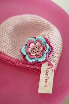 Love the neutral hat and colorful flower