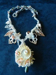 Beaded chambered nautilus with sliced shells, and pears, pendent is detachable and reversible, matching bracelet can added as an extension, has matching earrings.