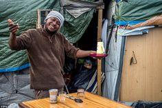 Toujours souriant: Un réfugié se tient en dehors de son domicile le jour avant Noël dans la jungle, ce qui a incité des sentiments forts en France