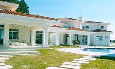 Casa com piscina, cor branca, paisagismo, telhado com telhas, varanda com pilares, gramado. Arquiteta Danyela Corrêa