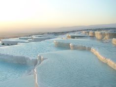 """Pamukkale  Southwest Turkey's Pamukkale (the """"cotton castle"""") is a natural site containing hot springs and travertines, terraces of minerals left by the flowing waters."""