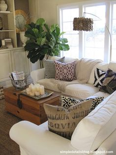 Love the mix of pillows..nothing matches. Candlescape on coffee table, basket holding magazines/ remote, white slip covered sofa Simple Details