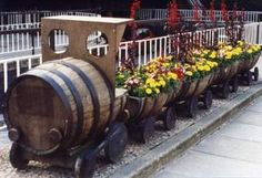 Whiskey barrels transformed into train and then planted. http://thegardeningcook.com/unique-garden-planters/