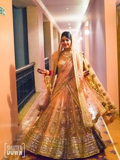 Peach and gold flared wedding lehenga embellished with gold shimmery sequins and motifs by the ace designer Sabyasachi Mukherjee.
