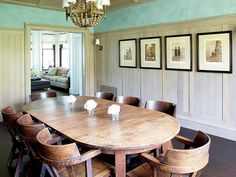 The home's casual dining room features a rugged captain's-style table and chairs and paneled walls.