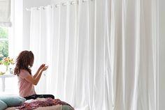 Chambre à coucher avec rideaux MERETE blancs fermés, dissimulant la penderie.