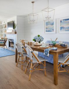 Beautifully appointed blue cottage dining room boasts Darlana Medium Lanterns hung above a honed stained dining table surrounded by Serena & Lily Riviera Side Chairs and a blue striped dining bench placed beneath pink and blue abstract art pieces mounted to shiplap trim.