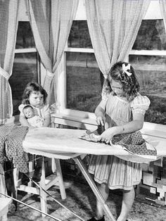 """Little girl using her """"play"""" iron  - 1950's"""