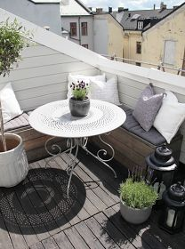 Small balcony idea: built-in bench w/ cushions and pillows, rod iron round table.