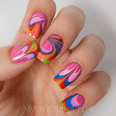 Candy colored water marble nail art design in pink, blue, orange and green polishes.