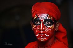 This man performs a traditional art form called theyyam. Theyyam is a ritual dance practiced in north Kerala, India.