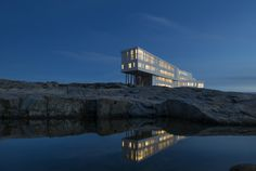 FOGO ISLAND INN, NEWFOUNDLAND At night, the Fogo Island Inn glows like a futuristic lighthouse. Perched on 50-foot stilts, it looms above a craggy outcrop on an island off the northeast coast of Newfoundland. Architect Todd Saunders designed the building with sharp angles and rough contours that echo the jagged landscape. Fogo Island Inn, Island Harbour, Canada