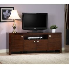 The elegant appeal of this wood entertainment center is the perfect addition to any living room decor. The entertainment unit easily allows a TV to rest on top, while the four drawers provided for added storage space help de-clutter any living room.