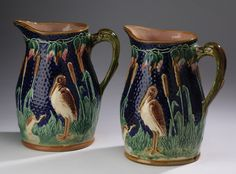 """Pair of majolica heron and cattail pitchers, having bas relief decoration on a cobalt ground and applied bird form handles, unmarked, 12""""h x 9.5""""w. Condition: One with repairs to base."""