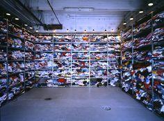 * Réserve du Musée des Enfants 1989 - Installation avec de la lumière Installation de vêtements d'enfants sur 6 rangs d'étagères métalliques dans l'ancienne réserve du Musée des enfants située au sous-sol. L'éclairage est constitué de 28 lampes de bureau fixées au sommet des étagères Tissus, métal, lampes - Christian BOLTANSKI (1944 - ) vit et travaille à Malakoff
